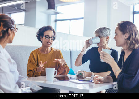 Un grupo de cuatro mujeres de negocios tras una discusión en la oficina. Mujeres profesionales sentados alrededor de una mesa y la reflexión sobre nuevo plan de negocio.