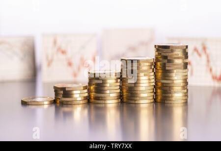 Aumento de los montones de monedas y gráficos con los precios de las acciones en el fondo mundial de uso |