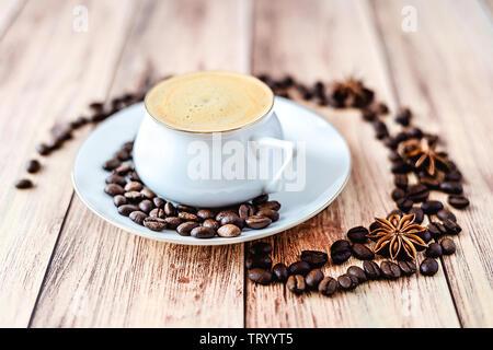 Vista cercana de una taza de café caliente sobre la mesa rústica de madera con granos de café derramado y anís. Espacio para el texto .