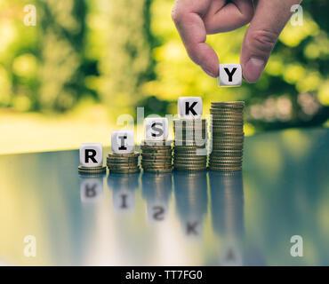 """Concepto de aumento de alto riesgo financiero. Coloca los dados en los grandes y crecientes pilas de monedas forman la palabra """"arriesgado""""."""