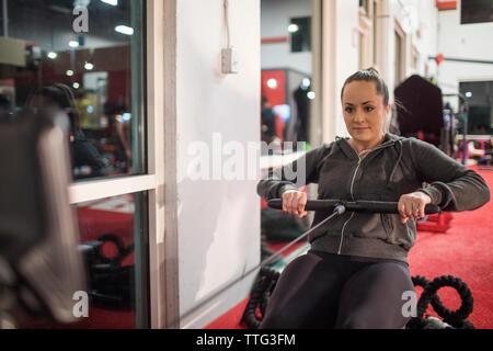 Colocar mujer milenaria en máquina de remo en el gimnasio