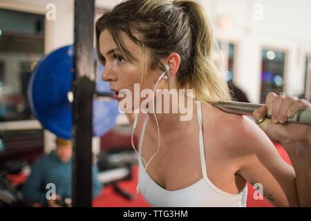 Vista recortada de mujer atractiva levantamiento barbell en gimnasio Foto de stock