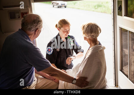 Paramédico comprobación de pulso del paciente por parte del esposo en la ambulancia