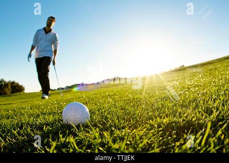 Hombre de pie en el campo de golf contra el cielo claro
