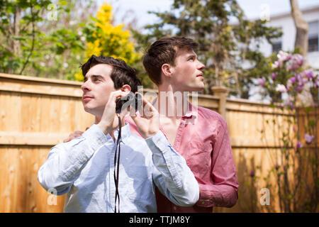 Los hombres gay con binoculares mirando a otro lado mientras está de pie en el patio