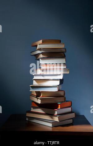 Pila de libros sobre la mesa de madera en cuarto oscuro Foto de stock