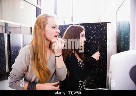Amigos haciendo maquillaje en sanitario en high school Foto de stock