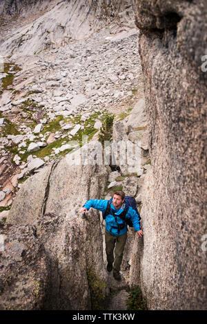 Un alto ángulo de visión del hombre senderismo sobre formaciones rocosas