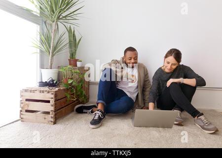Gente de negocios sonriendo utilizando el portátil mientras está sentado en el piso en la oficina creativa