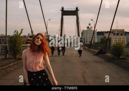 Chica con el pelo rojo caminando sobre el puente en la ciudad
