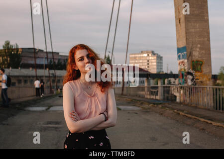 Retrato de mujer joven con el pelo rojo de pie en el puente en la ciudad