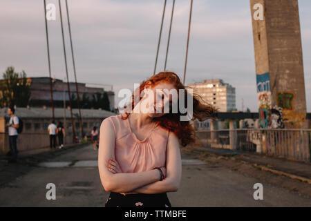 Mujer joven caminando sobre el puente en la ciudad