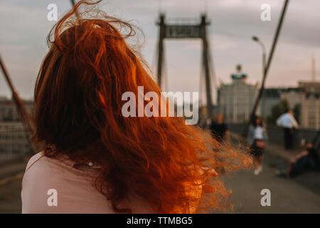 Vista trasera de la mujer con el pelo rojo caminando sobre el puente en la ciudad
