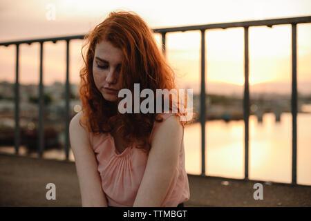 Retrato de mujer joven con el pelo rojo sentada en puente al atardecer