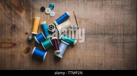 Alta Vista angular de carretes coloridos con dedales y botones en la mesa de madera en el taller