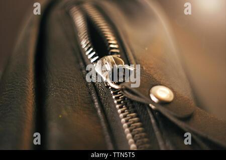 Cremallera de metal en el bolsillo del bolso de cuero negro, iluminado por la luz