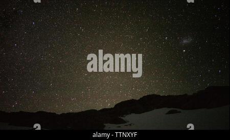 Vista panorámica del campo cubierto de nieve contra el campo de estrellas por la noche Foto de stock