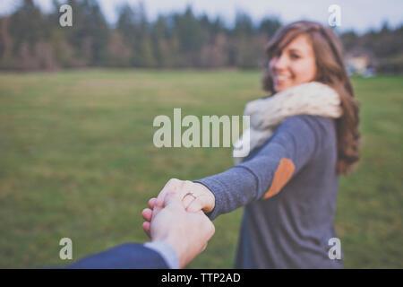 Mano recortada del marido sosteniendo la mano de esposa