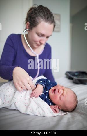 La comadrona examinar bebé recién nacido chica con el estetoscopio en la cama en casa