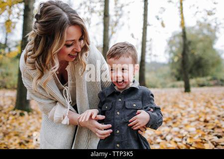 Alegre madre jugando con lindo hijo en el bosque durante el otoño
