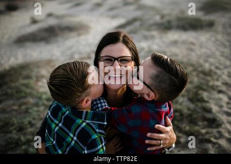 Alto ángulo vertical de madre feliz ser besado por lindos hijos en la playa durante la puesta de sol