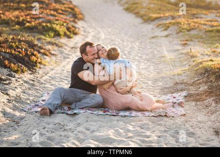 Felices padres abrazando hijo mientras está sentado en la arena en la playa durante la puesta de sol