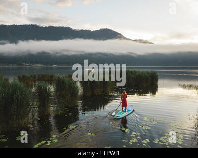 Una mujer sobre un lago paddleboarding