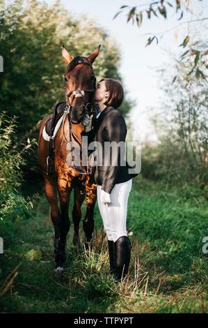 Vista lateral del jinete femenino besar a caballo mientras está de pie sobre el césped Foto de stock