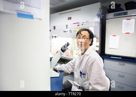 Retrato de mujer senior scientist utilizando microscopio en laboratorio