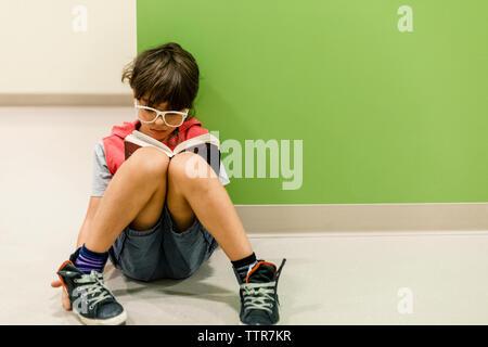 Niño con gafas leyendo sentado en el piso contra la pared inclinada
