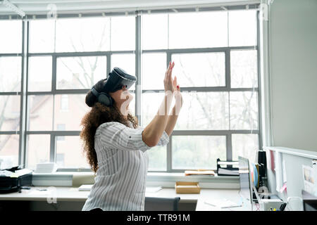 La empresaria vistiendo simulador de realidad virtual en la oficina