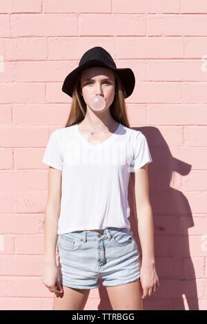 Retrato de una adolescente que sopla chicle mientras está de pie contra la pared