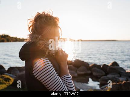 Vista lateral de la mujer con los ojos cerrados en Lakeshore permanente contra el cielo despejado durante la puesta de sol