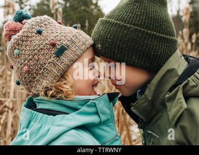 Hermano y hermana tocar jefes jugando y sonriendo en invierno