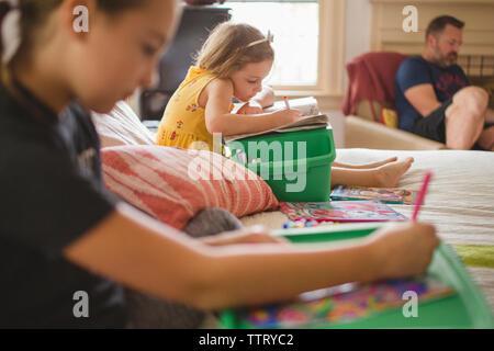 Hermanas dibujo mientras sentada en la cama en casa contra el padre.