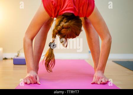 Una mujer prácticas yoga sobre una esterilla de yoga