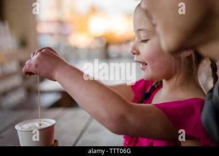 Una niña se sienta feliz con su padre en la mesita de café de cacao de agitación