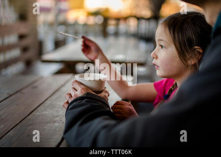 Un niño se sienta con su padre en un café al aire libre al atardecer