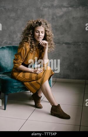 Hermosa joven mujer está rizado en la oficina en un vestido retro