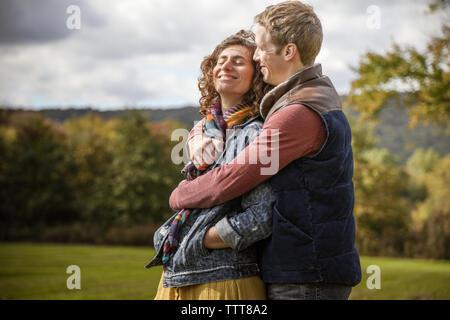 Pareja abrazada en abrazo sonriendo y riendo con los ojos cerrados en el campo