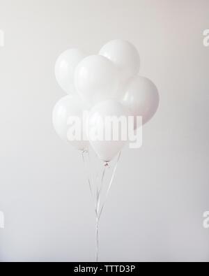 Montón de globos contra la pared Foto de stock