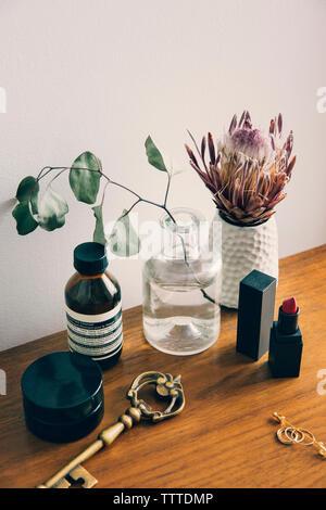 Un alto ángulo de visualización de productos de belleza con florero en la mesa