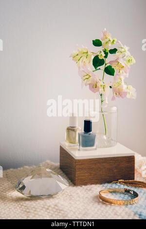 Esmalte de uñas con joyas y cristal por florero en la mesa