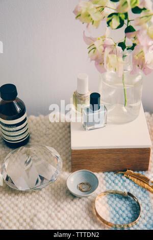 Productos de belleza con joyas y cristal por florero en la mesa