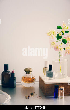 Productos de belleza con joyas y florero en la mesa contra la pared blanca