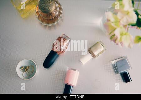 Un alto ángulo de visualización de productos de belleza con joyas de florero en la mesa