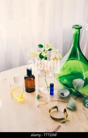 Un alto ángulo de visualización de productos de belleza y joyas de florero en la mesa