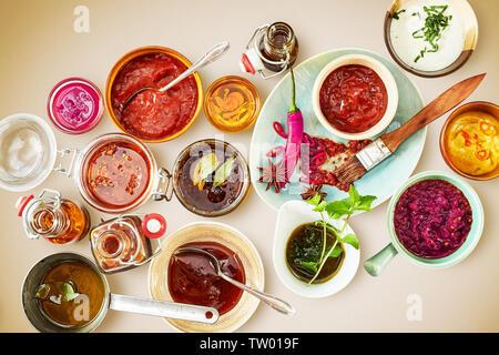 Vista aérea de tazones y platos con salsa roja y cucharones. Selección de pimientos y hierbas en placas.