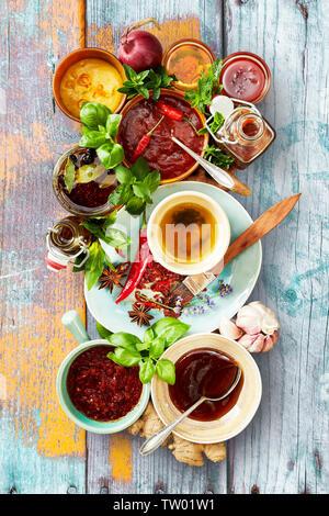 Selección de diferentes salsas y aderezos en tazones listos para una barbacoa con albahaca fresca y hierbas sobre un fondo multicolor rústica madera visto arriba ¿