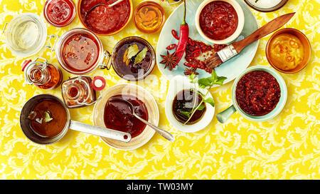 Vista aérea de chutney rojo y salsa con otros condimentos en rojo sobre fondo amarillo de tazones estampados